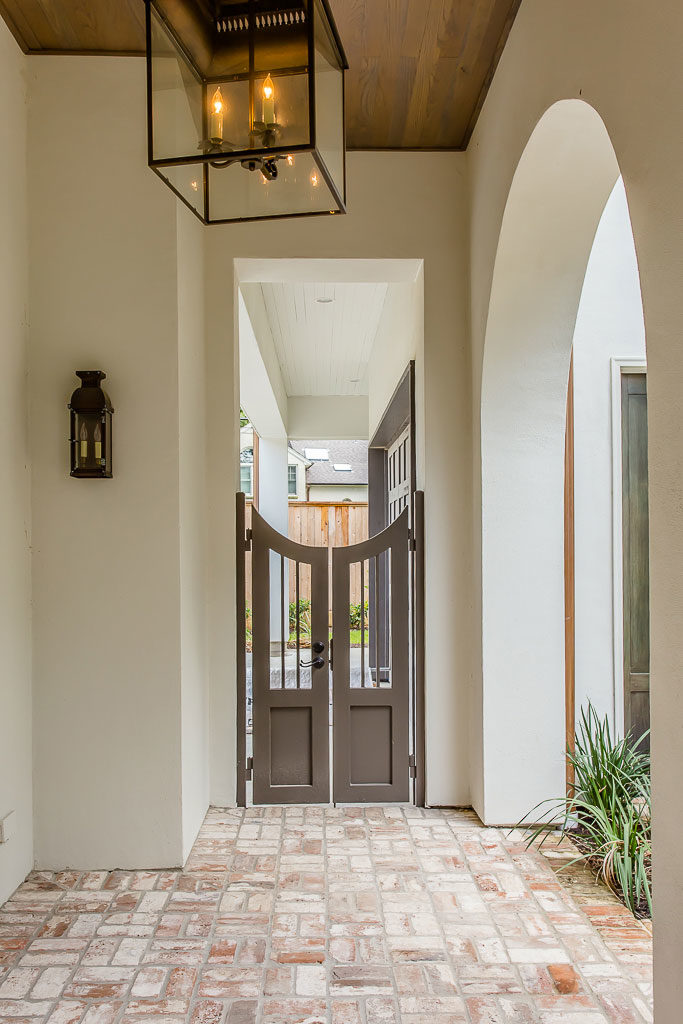 brick porch with iron and glass sconces and chandeliers, custom wood gate