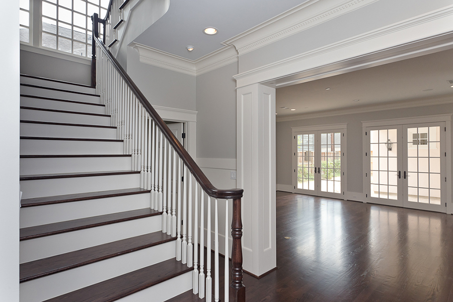 large starecase with stained banister, woodwork and large french doors
