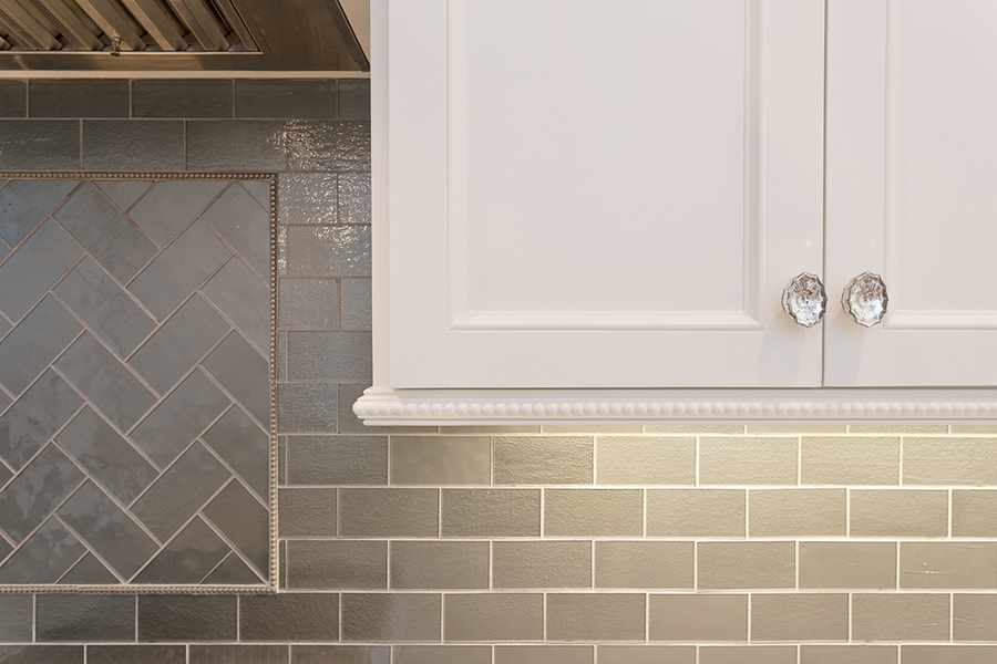 custom kitchen with glass knobs and gray-green subway tile