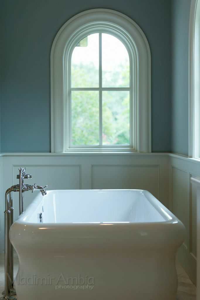 custom Mediterranean Revival style home bathroom with tub and rounded window