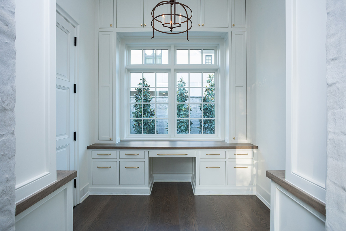 home office with built in desk, chandelier and large withdow