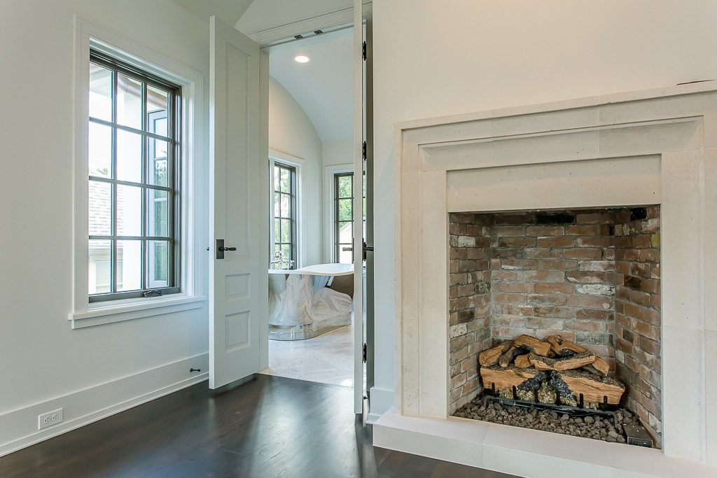 custom master suite in River Oaks, antique brick gas log fireplace with limestone mantle